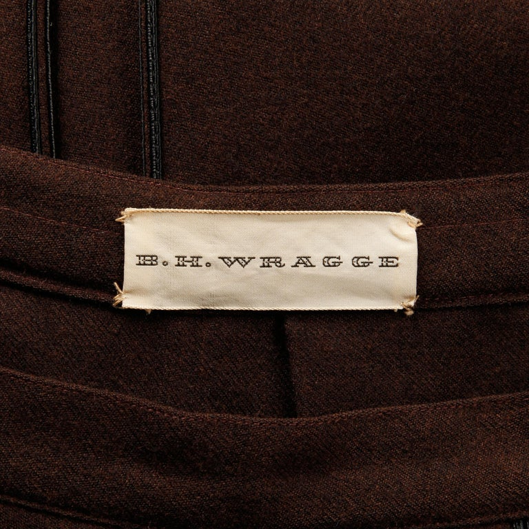 Early 1960s vintage pleated skirt by B.H. Wragge. Brown wool with black cord trimmed box pleats. Unlined with side metal zip and hook closure. Fits like a modern size small. The waist measures 25