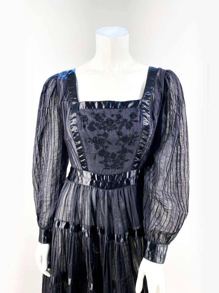 1960s Peasant/Bohemian Dress with a sheer pin pleated black cotton with satin striping, an embroidered torso, full circle skirt, and cuffed sleeves.
