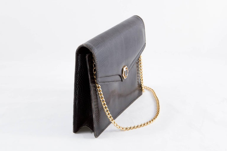 1960s unsigned black  evening bag featuring a lizard leather outside, an inside black leather lining, a detachable gold tone shoulder chain, a front snap closure, inside 2 small pockets.  In excellent vintage condition. Made in France. Measurements: