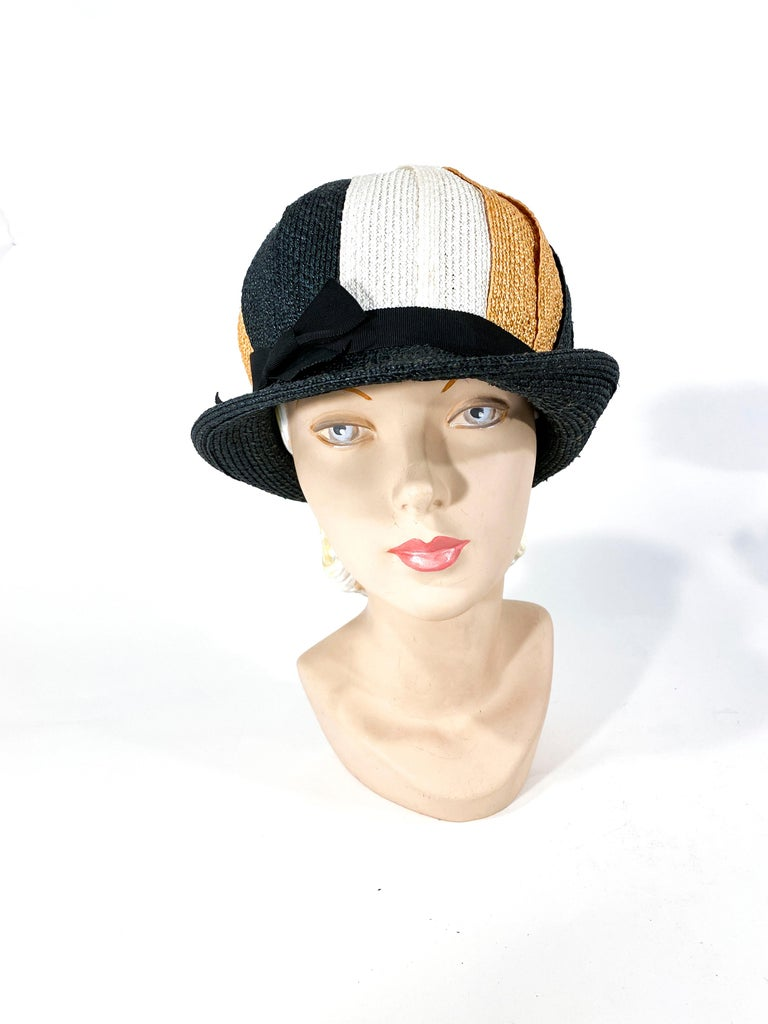 1960s woven raffia hat in black, gold, and cream in a pinwheel pattern. It has a very mod