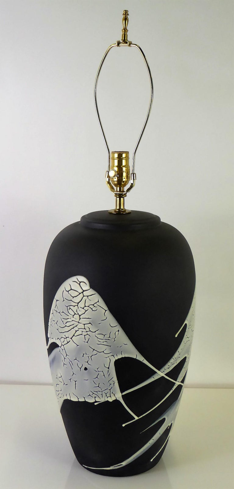 1960s lava glaze ceramic table lamp with a matte black finish and splashes of white lava glaze. An oil jar shape, it has been rewired and with a new brass UL three level socket. Takes medium base bulbs.