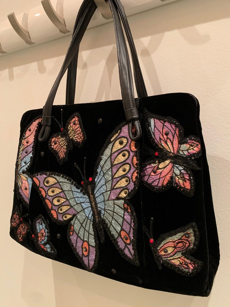 A charming and whimsical 1960s black velvet handbag with colorful butterfly appliques over one side.  Center snap compartment and side bucket compartments. Faux leather handle.