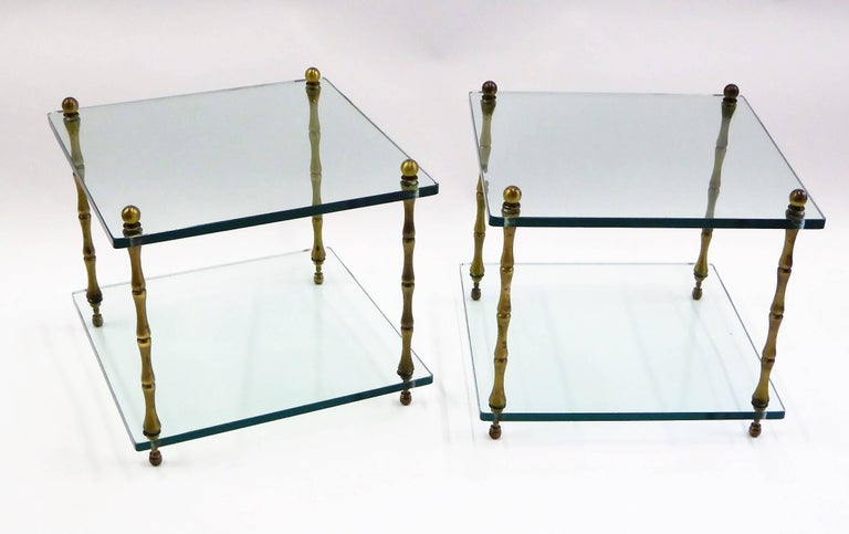 Elegant and fun brass legged faux bamboo glass tables perfect as occasional and side tables. Featuring two glass levels each with 1/2 inch thick glass supported by four upright brass faux bamboo shaped legs. 1960s Maison Bagues style end