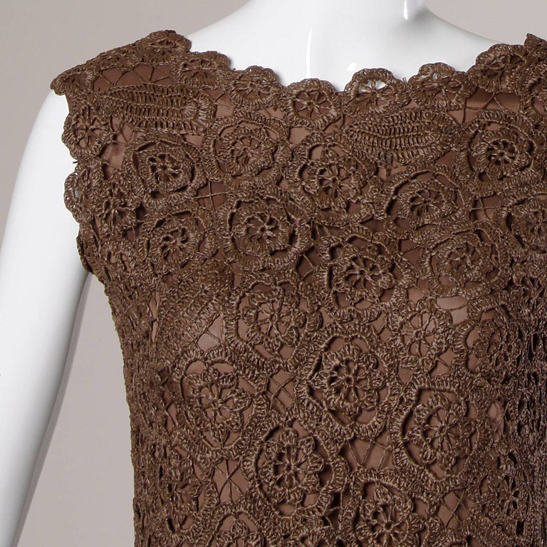 Hand crocheted brown raffia shift dress with a scalloped design and metal zipper.  Details:  Fully Lined Back Metal Zip Closure Marked Size: 12 Estimated Size: Medium Color: Brown Fabric: Hand Crocheted Raffia Label: Not Marked  Measurements:  Bust: