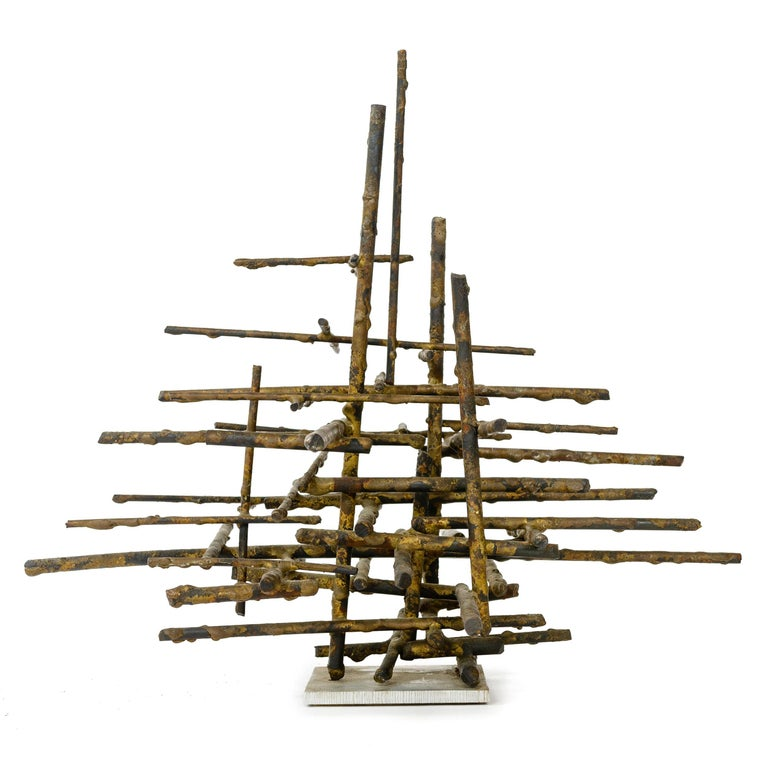 Brutalist tabletop sculpture being a linear assemblage of bronze twig like rods of varying lengths stacked on a square aluminum base. Letters 'HF' and '64' etched in to the base in a modern sans serif font.