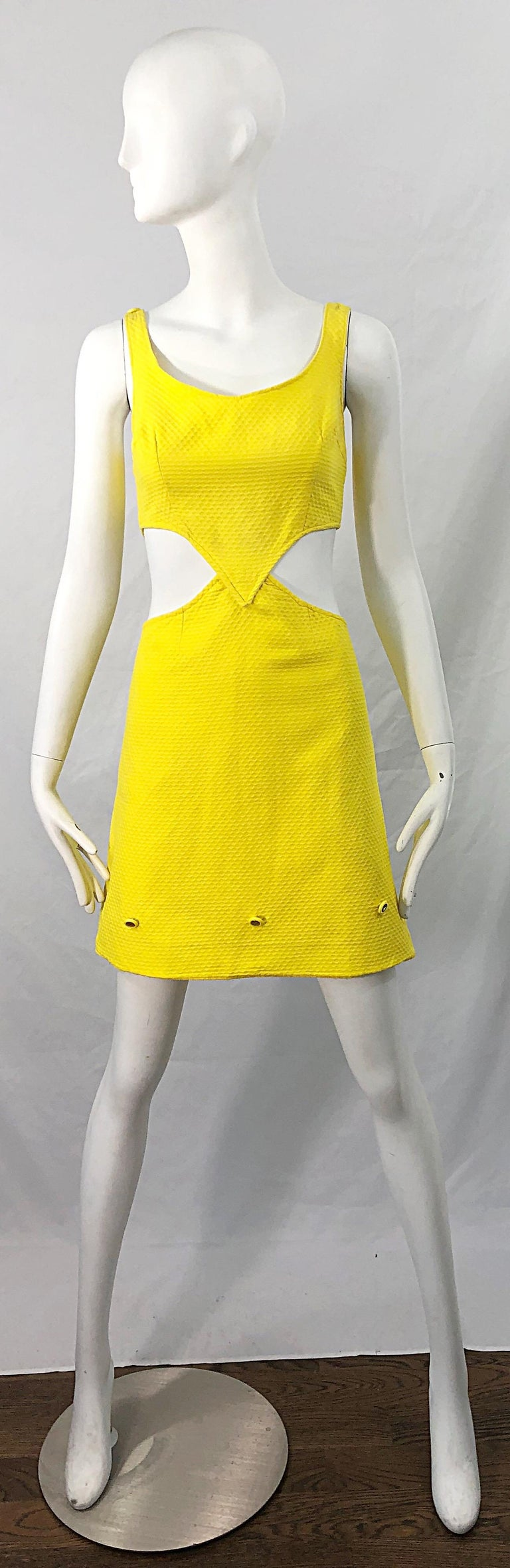 Chic 1960s canary yellow honeycomb pique cotton cut-out A Line dress ! Features cut-outs at each side of the waist. Adjustable gold glitter buttons at each shoulder to adjust length. Three of the same gold buttons along the front bottom of the
