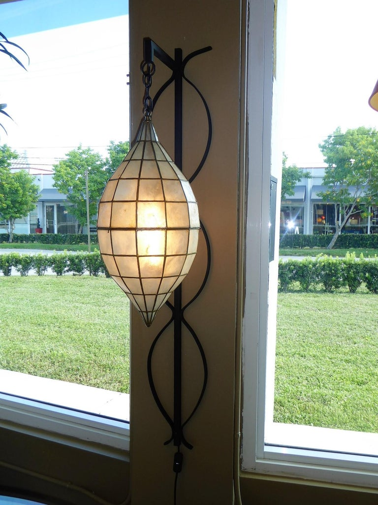 Unique and stunning, with a nod to Tony Duquette style, this wall sconce or light has a large Oblique Spheroid or teardrop form Capiz Shell pendant light hanging from a shaped wrought iron back, wall mounted. Completely restored, the wrought iron
