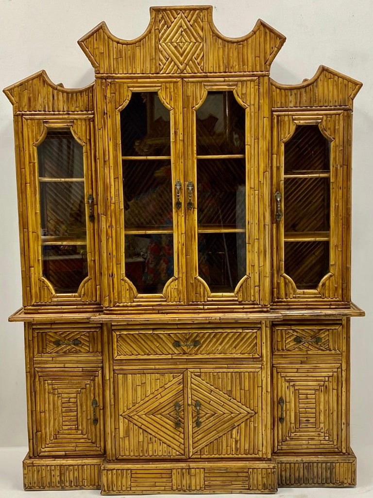 This is a 1960s pencil bamboo cabinet with Chinese Chippendale styling. It is in two pieces for easy shipping, and it is unmarked. I have acquired 4 bun feet for this cabinet and can include if so desired. A great piece!