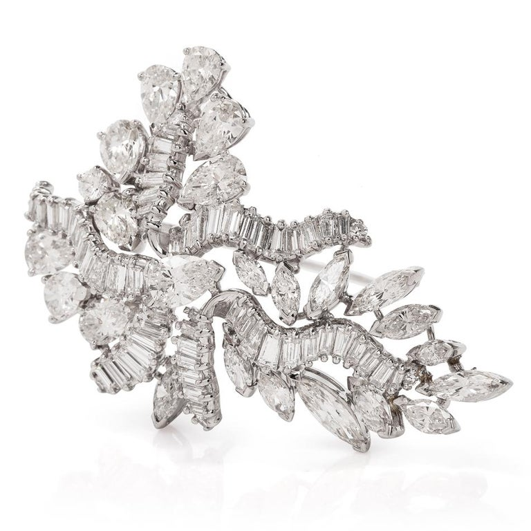 This botanically inspired swirl diamond brooch is crafted in solid platinum, weighing 20.4 grams and measures 54mm long x 34mm wide. Channel-set with 72 baguette shaped diamonds, weighing approximately, 4.32 carats, graded G-H color and VS clarity.