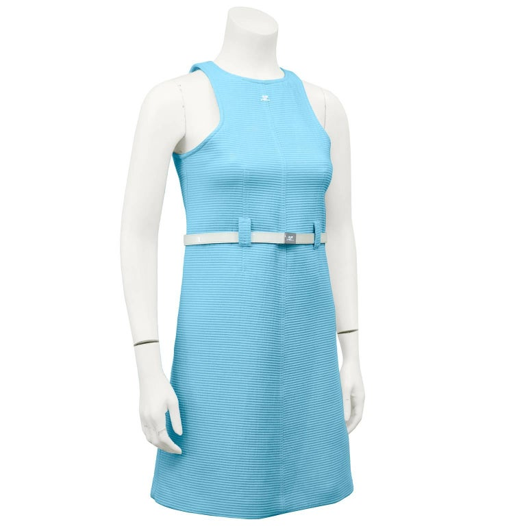 Adorable 1960s Courreges cotton baby blue ribbed day dress. Razor neckline with white embroidered Courreges logo. Belt loops and white patent loose fit leather belt at waist with sliver hardware and Courreges logo. Excellent vintage condition.
