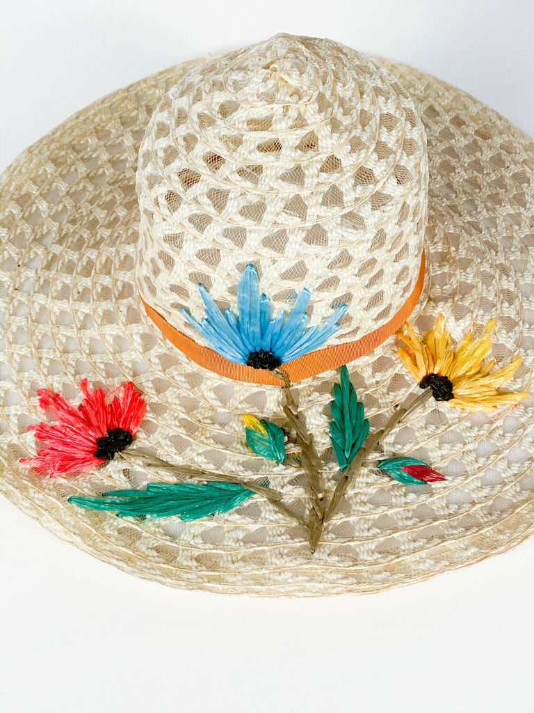 1960s Creme Raffia Beach Hat with Raffia Flower hand-embroidery in blue, pink and yellow finished with an orange gros-grain band.