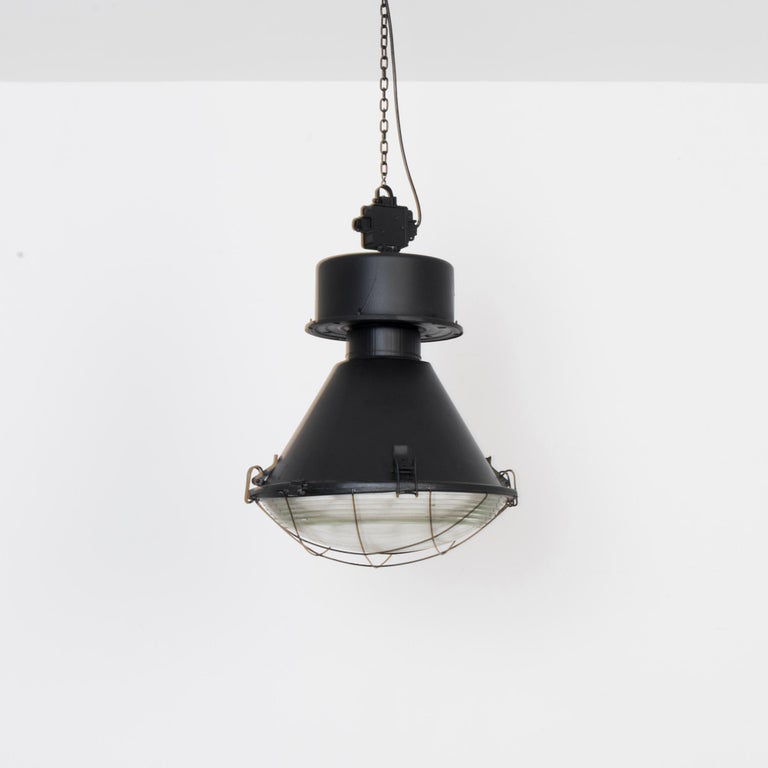 Original finishes and hardware, re-electrified and fitted for E26 socket. Enclosed in thick textured glass, this large scale industrial pendant blends clean lines with bold geometric forms. A sturdy and stylish industrial touch in your space.