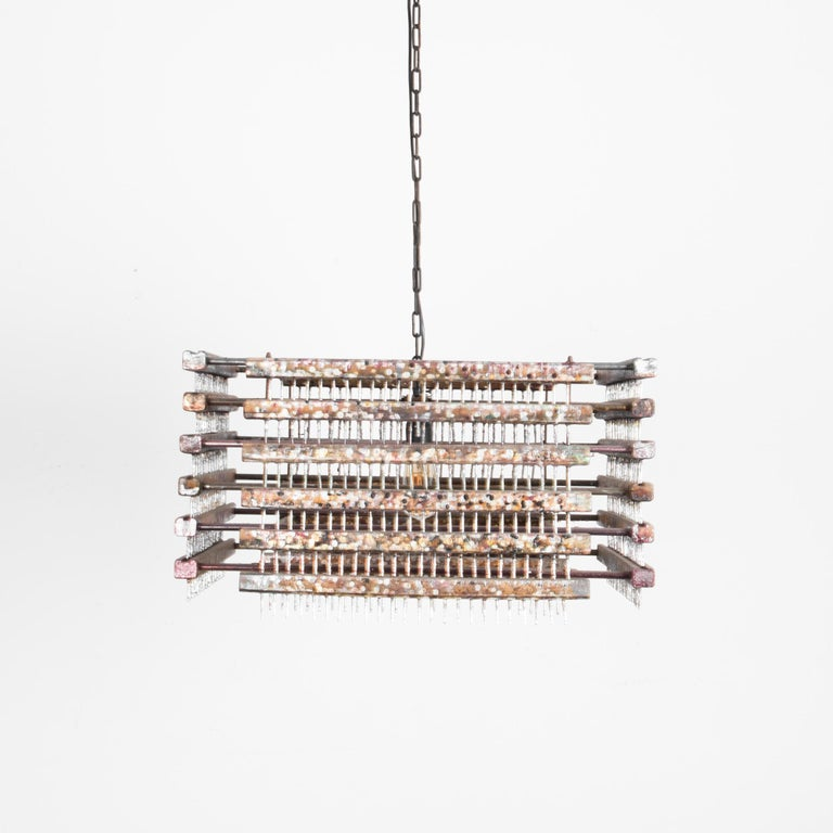 This metal pendant light was made in Czechia in the 1960s.  A ceiling chain sustains a square light fixture made of a grid of metal bars for a stark, brutalist silhouette. The industrial sensibility of the interlocking metal bars is softened by