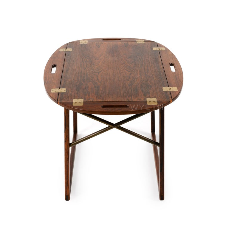A finely crafted tray table in rich rosewood with a removable tray top. Brass hinged edges flip up to convert to handles.