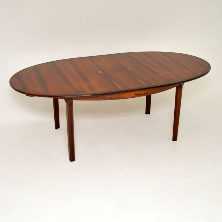 A beautiful vintage dining table, made in Denmark and dating from the 1960s. This is of great quality, it has a beautiful color and stunning wood grain patterns.  This has an extra leaf to extend the dining area, it folds down and stores under the