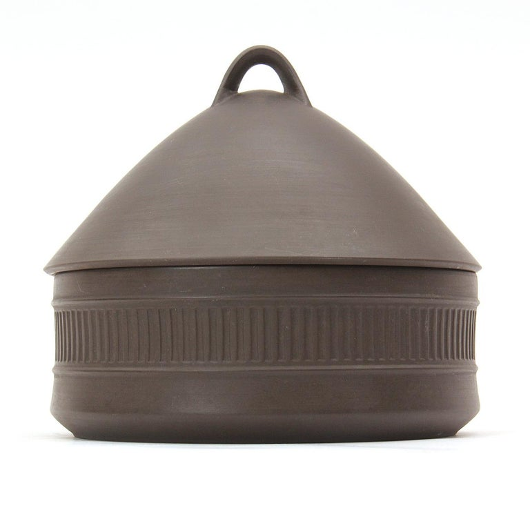 A flame stone ceramic casserole pot with a domed lid, matte exterior and cream glazed interior.