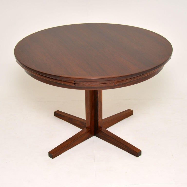 A stunning Danish wooden dining table by Dyrlund, this is the famous flip flap lotus table, it dates from the 1960's. This is a very rare version, with a single column pedestal and a slightly smaller top and leaves than normal. The quality is