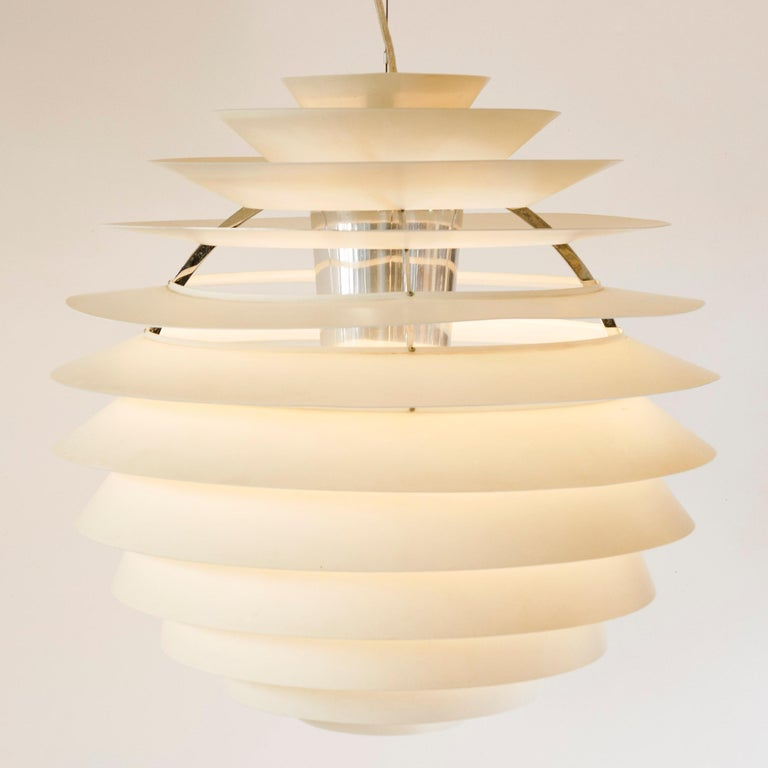 A chandelier comprised of concentric white enameled aluminum louvres, emanating from a central internal reflector.