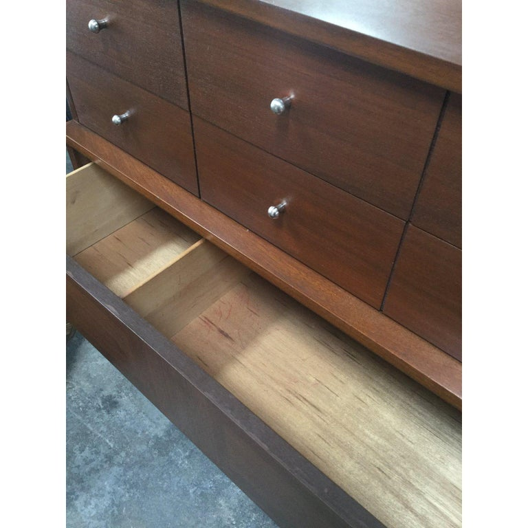 Stunning midcentury dresser! Wonderful wood details with a lovely walnut stain. 5 drawers, with 6 silver knobs giving a 1960s style!