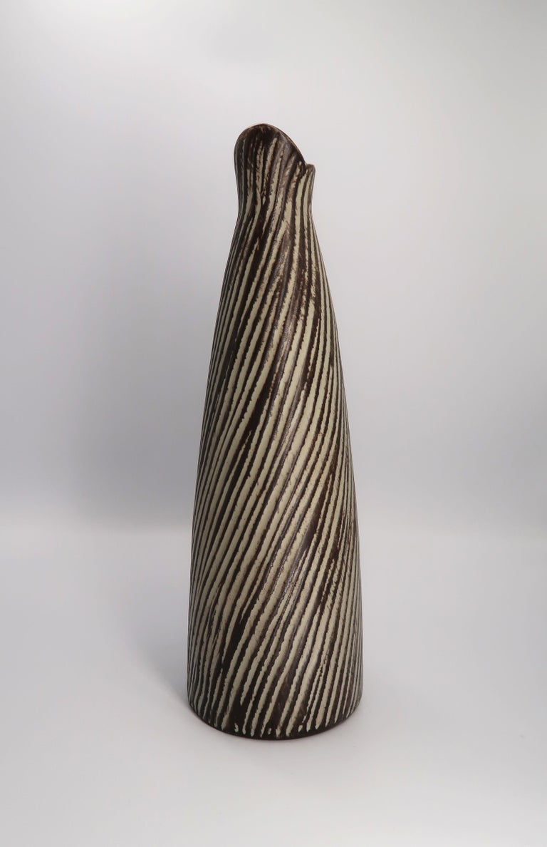 Danish Mid-Century Modern ceramic vase/pitcher with bamboo handle attached with bast. Grey and dark brown glazed relief stripes run diagonally across the whole vase. Designed and handmade by Danish ceramic artist Jette Helleroe. Signed under base.