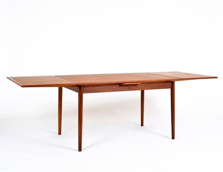 Slim, sleek and very stylish, this 1960s Danish modern draw leaf teak extending dining table was manufactured by AM Møbler (Ansager Møbler) Denmark. Seats 6 when closed (130 cm) and up to 10 when extended (238 cm).
