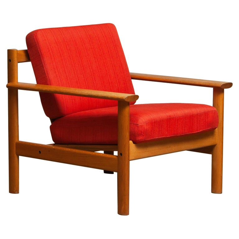 Firm Danish oak lounge easy chair in the manner of Poul Volther from the 1960s. The cushions are a metal base with spring and still upholstered with the original fabric. Overall condition is good. Note that we have two similar chairs. See the