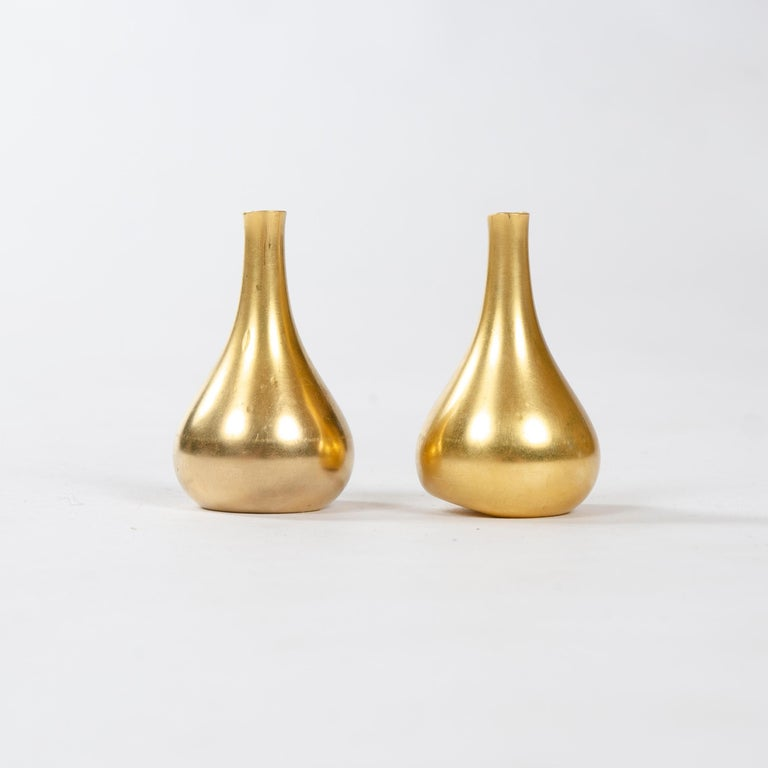 A pair of petite cast bronze candleholders with weighted and chamfered bottoms. Each stamped