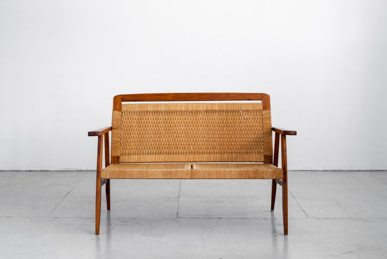 Beautiful vintage Danish bench with angled teak legs and tightly woven rope seat. Back of seat tilts to provide a perfect angle of comfort. Great age and coloring throughout.