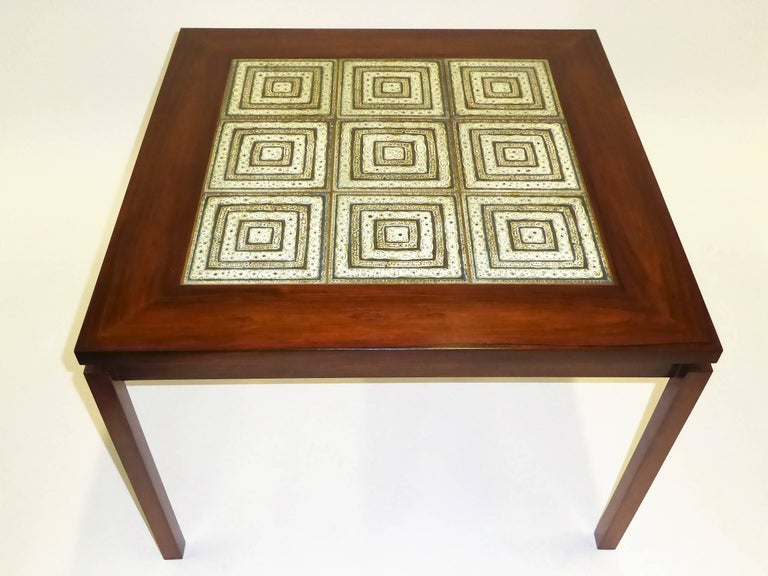 Beautifully figured Rosewood highlights this table as well as the centered Nils Thorsson tiles, probably Royal Copenhagen. Cantilevered positioned legs add to its charm, extending out from the apron frieze, the top overhanging like an eave. Restored