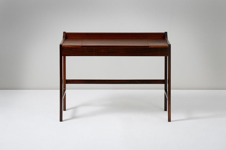 Danish cabinetmaker  Dressing table, circa 1960  Dressing table made from highly figured Brazilian rosewood with fold-down mirror on brass fittings.   Measures: H 77cm, D 50cm, W 55cm, SH 44cm.