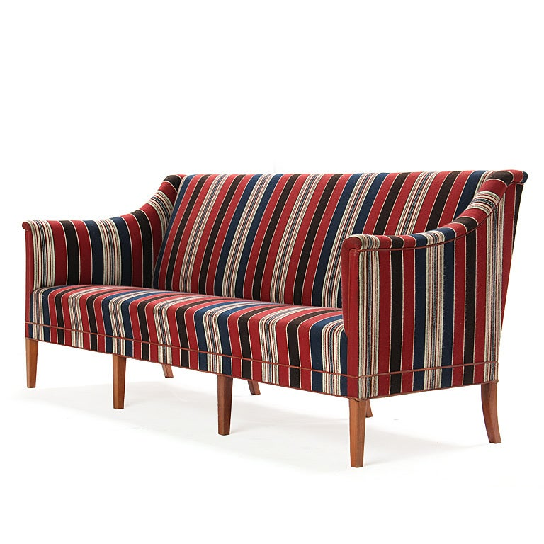 A majestic sofa having a sculptured body resting on eight (8) tapered mahogany legs, retaining the original red, navy and beige striped wool fabric. Designed in the 1940s and manufactured in the 1960s.