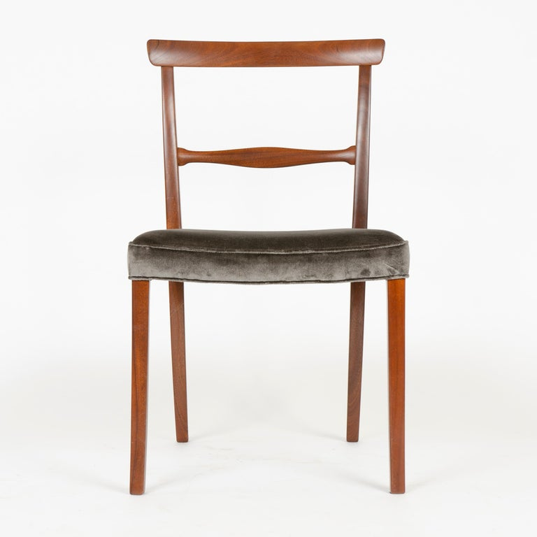 Designed in 1962, this expertly crafted dining chair by Ole Wanscher was built in the cabinet shop of A. J. Iversen of Brazilian rosewood in the 1960s. A graceful, minimal design consisting of only essential elements; a slight crest rail which