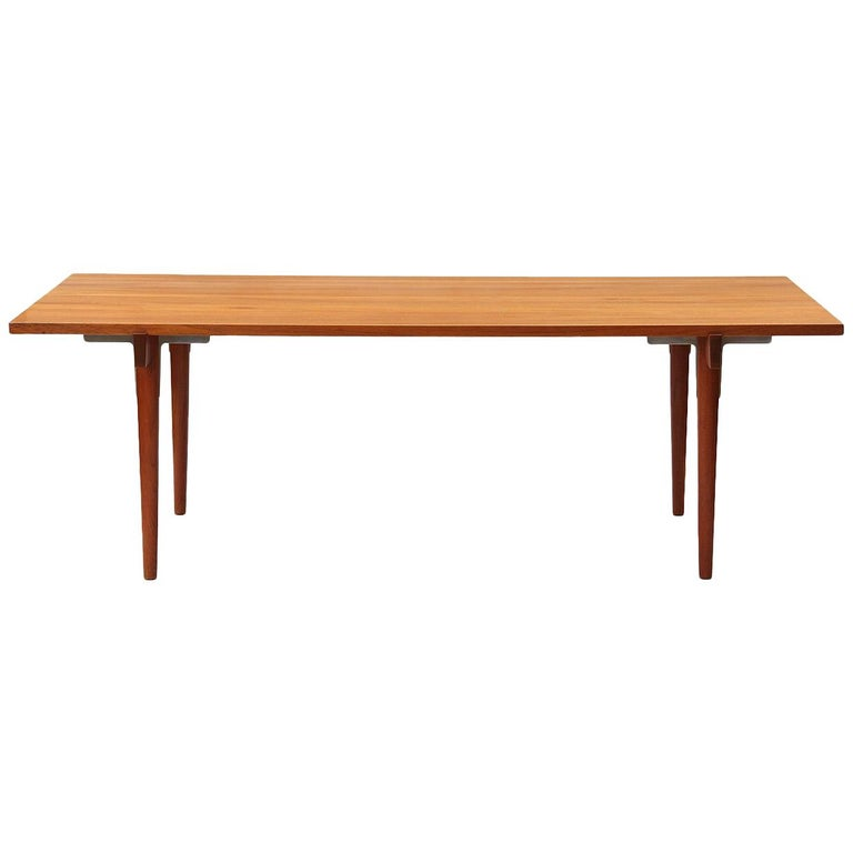 A rare Danish modern solid teak table / desk with clean sides and a recessed apron with chromium hardware. Designed by Hans Wegner, crafted by Johannes Hansen in the 1960s.