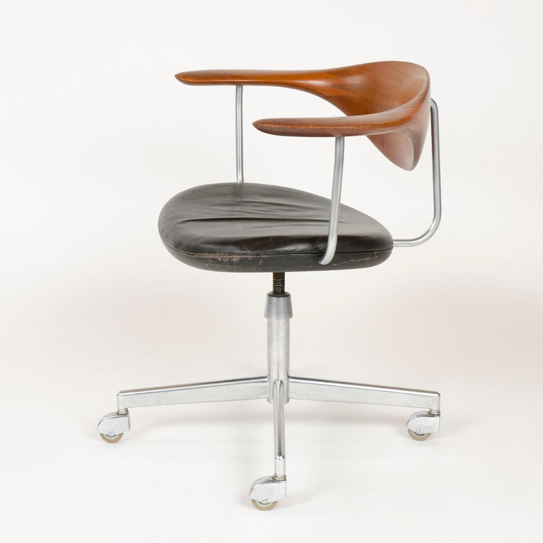 A superb swiveling desk chair having a hand-sculpted floating teak backrest and black leather seat, on a chrome base with hooded casters.