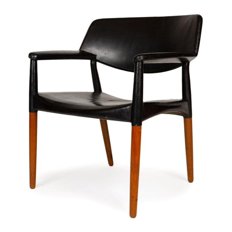 A comfortably wide (27.5'') conference chair in solid teak and black leather. The designers characteristically clad the upper half of the chair in black leather while the exposed wood of the lower half is in natural teak. A gentle curve under the