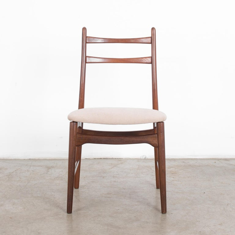 This teak chair was made in Denmark, circa 1960. Four tapered legs, angled slightly outward, construct the smooth, clean lines of this midcentury piece of furniture. Doubling as a dining or desk chair. A pair of gently curved rails sits in the upper