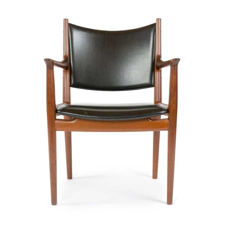 An elegant handcrafted dining chair, having an exposed teak frame and leather upholstery.