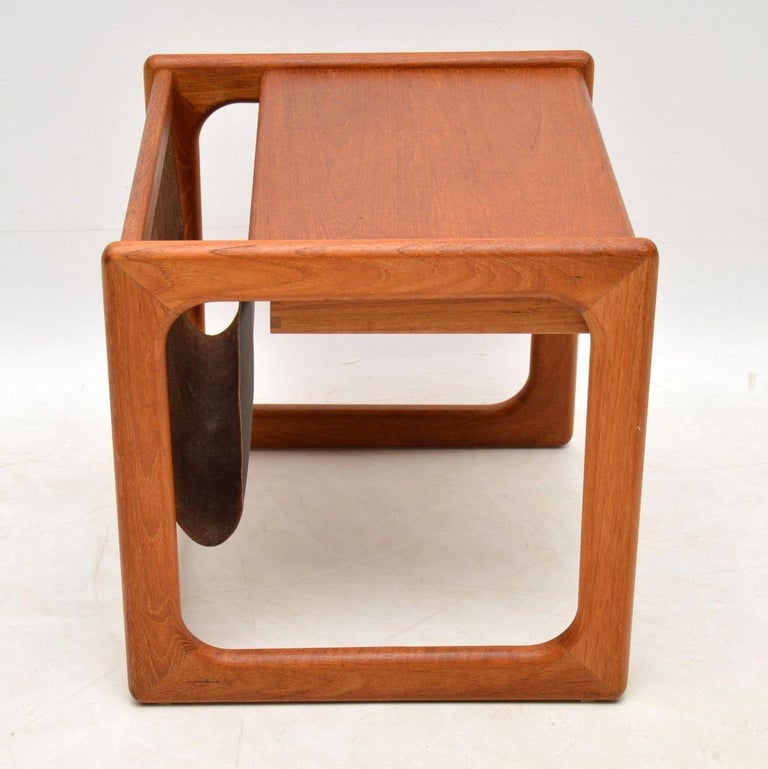 A stylish and top quality vintage Danish side table in teak, with a built in leather magazine rack, it dates from the 1960s-1970s. This is really well made, and is in great condition for its age, with only some extremely minor wear here and