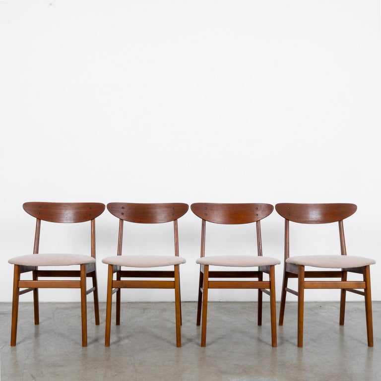 This set of four chairs from Denmark circa 1960 is Classic Scandinavian Modern design. Freshly re-upholstered and looking like the seat backs were scooped raw off the side of a tree, the sleek clean lines of these chairs will add grace to any