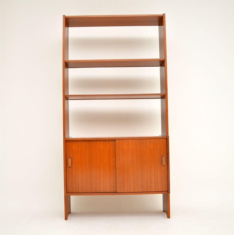 A smart and stylish vintage Danish bookcase in teak, this dates from the 1960s. It's in lovely original condition, with only some light surface wear and a few very minor marks here and there. The lower cabinet has two sliding doors, and has a