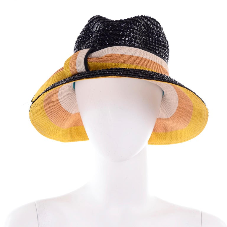 This is a deadstock vintage Yves Saint Laurent straw hat with the original tags still attached. This is a great glossy black woven straw hat with yellow, tan, and cream striped ribbon detail.. The underside of the hat is the same striped colors as