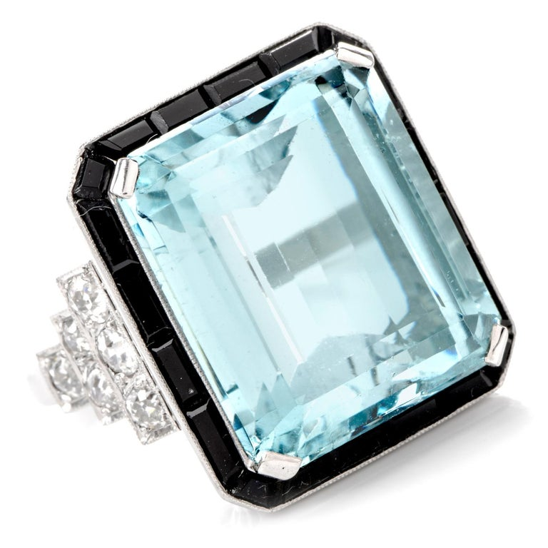 This 1960's  Vintage Diamond Aquamarine Onyx ring is inspired in Art Deco and hand crafted in Platinum. Prominently featured in the center is an approximately 28.10 carats of flawless genuine  Aquamarine. It is surrounded by channel set rectangular