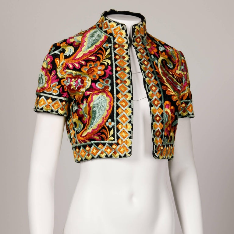 Stunning vintage Donald Brooks for I. Magnin cropped bolero jacket with a heavily embroidered floral paisley design. Short sleeves and single front hook closure. Fully lined. There is no marked size, but this fits like a modern XS-S. The bust