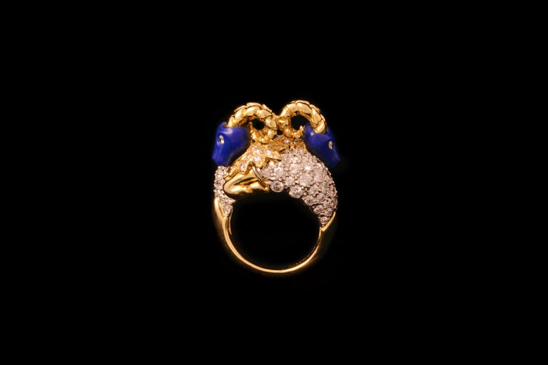 A pavé-set diamond, carved lapis lazuli and 18 karat gold crossover ring with stylized rams, by Donald Claflin for Tiffany & Co., 1960s.  This ring is size 7 1/4 and it measures 0.75