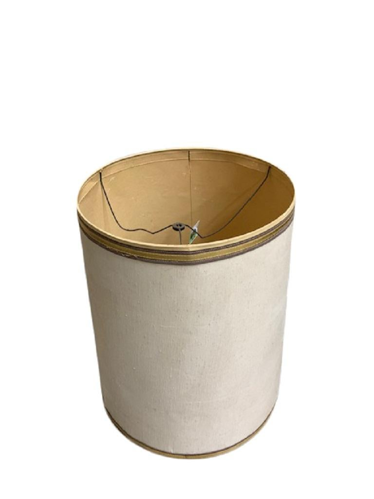 A linen drum-shaped lamp shade. Made of off-white linen with gold grosgrain ribbon trim on top and bottom edges, US, circa 1960.