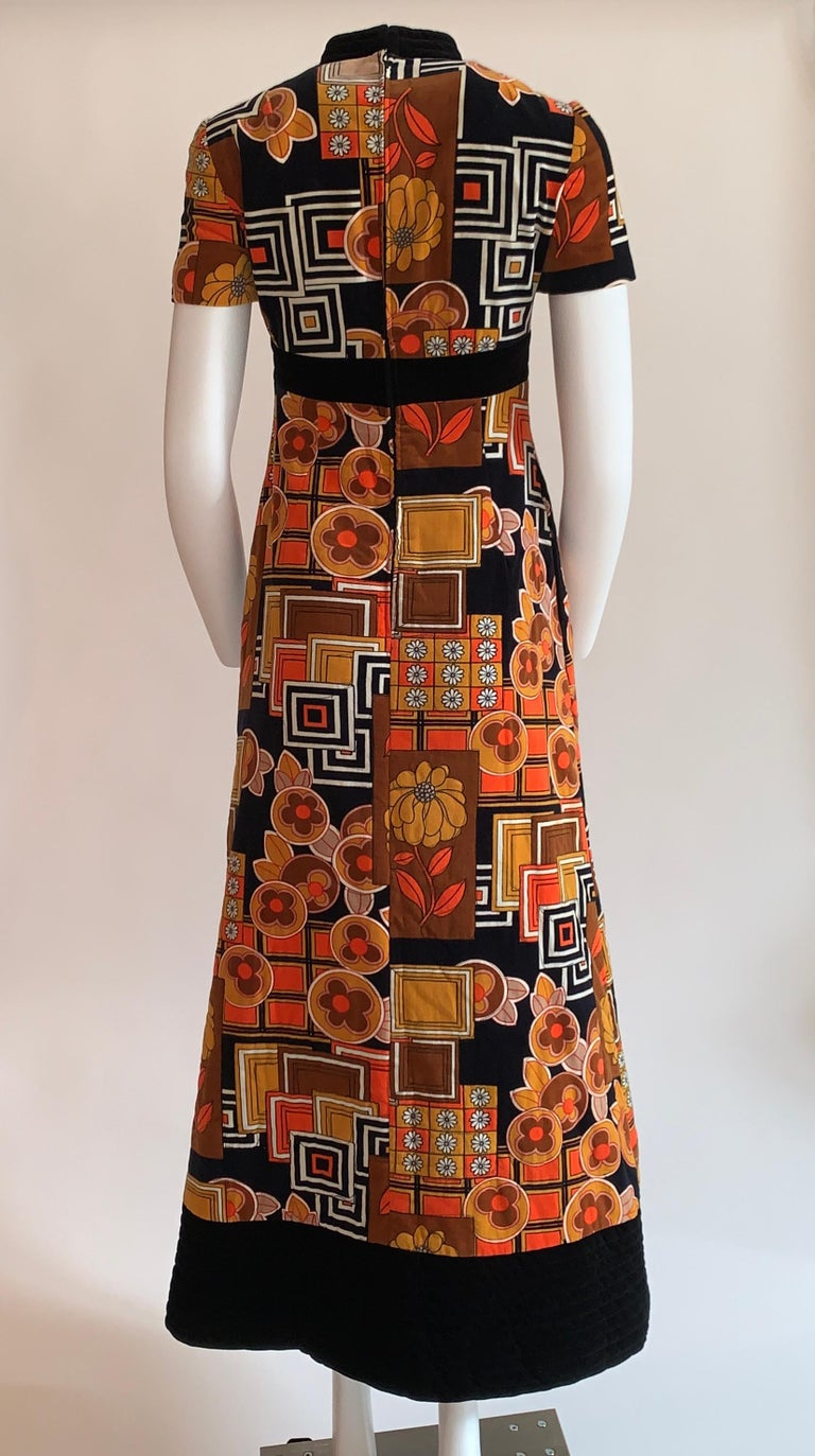Vintage 1960s I. Magnin & Co. by Dynasty orange, brown and black floral print A-line quilted velvet maxi dress. Psychedelic floral and geometric pattern. Short sleeves and cheongsam inspired collar. Quilted band at waist. Back zip and hook and eye
