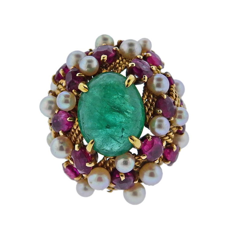 Circa 1960s 18k gold cocktail ring, set with 12.5mm x 9.9mm emerald cabochon in the center, surrounded with rubies and pearls. Ring size - 4.5, ring top - 25mm x 23mm. Weight is 13.6 grams.
