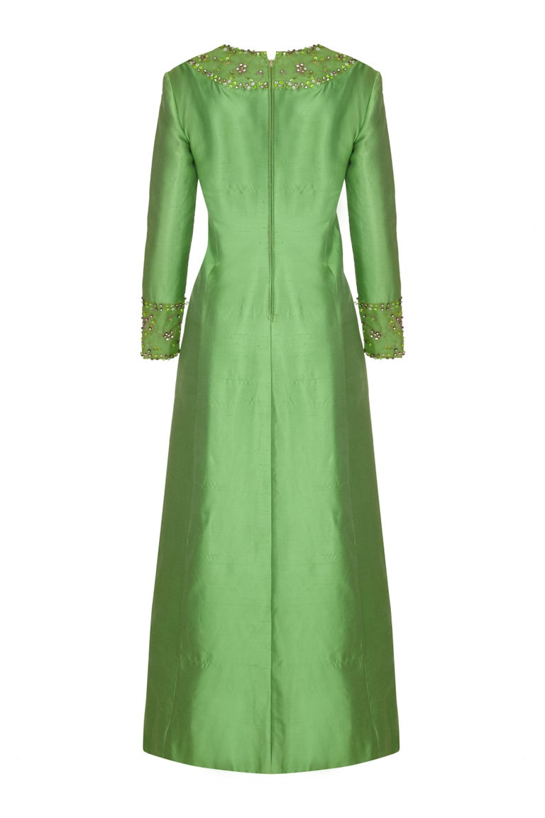 This stunning full length silk vintage dress in emerald green is by American label Gino Charles for Malcolm Starr and is of superb quality. This opulent piece has intricate beading with prong set rhinestone embellishment in green, pink and crystal