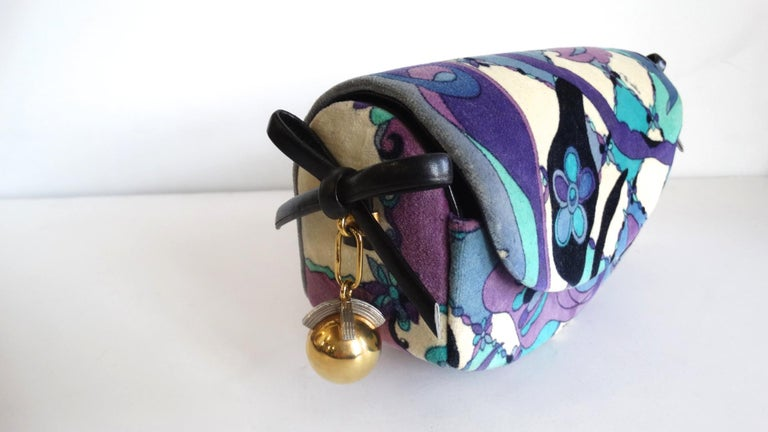 More Pucci Please! Circa 1960s, this Pucci clutch features one of his many signature abstract floral patterns in teal, and shades of purples and blues. The sides include dark navy leather bows and a gold plated ball charm. Front flap opens to reveal