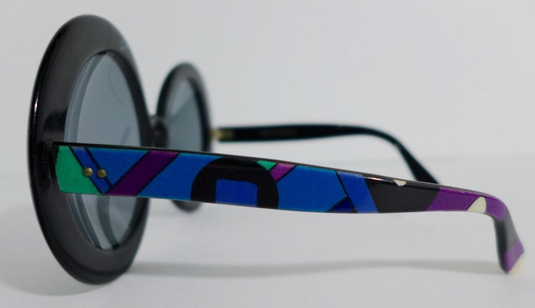 These Emilio Pucci round plastic sunglasses feature a classic blue, green, and purple print. The lenses are black. Made in France.   Measurements in Inches:  Width: 6.5  Height: 3 Length: 5.5